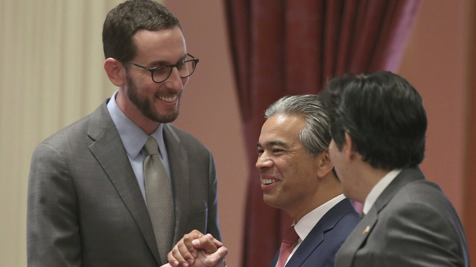 State Sen. Scott Wiener, D-San Francisco, left, receives congratulations from Assemblyman Rob Bonta, D-Alameda, center, and Sen. Kevin de Leon, D-Los Angeles, right, after passage of the bill Friday in Sacramento.  Rich Pedroncelli/AP