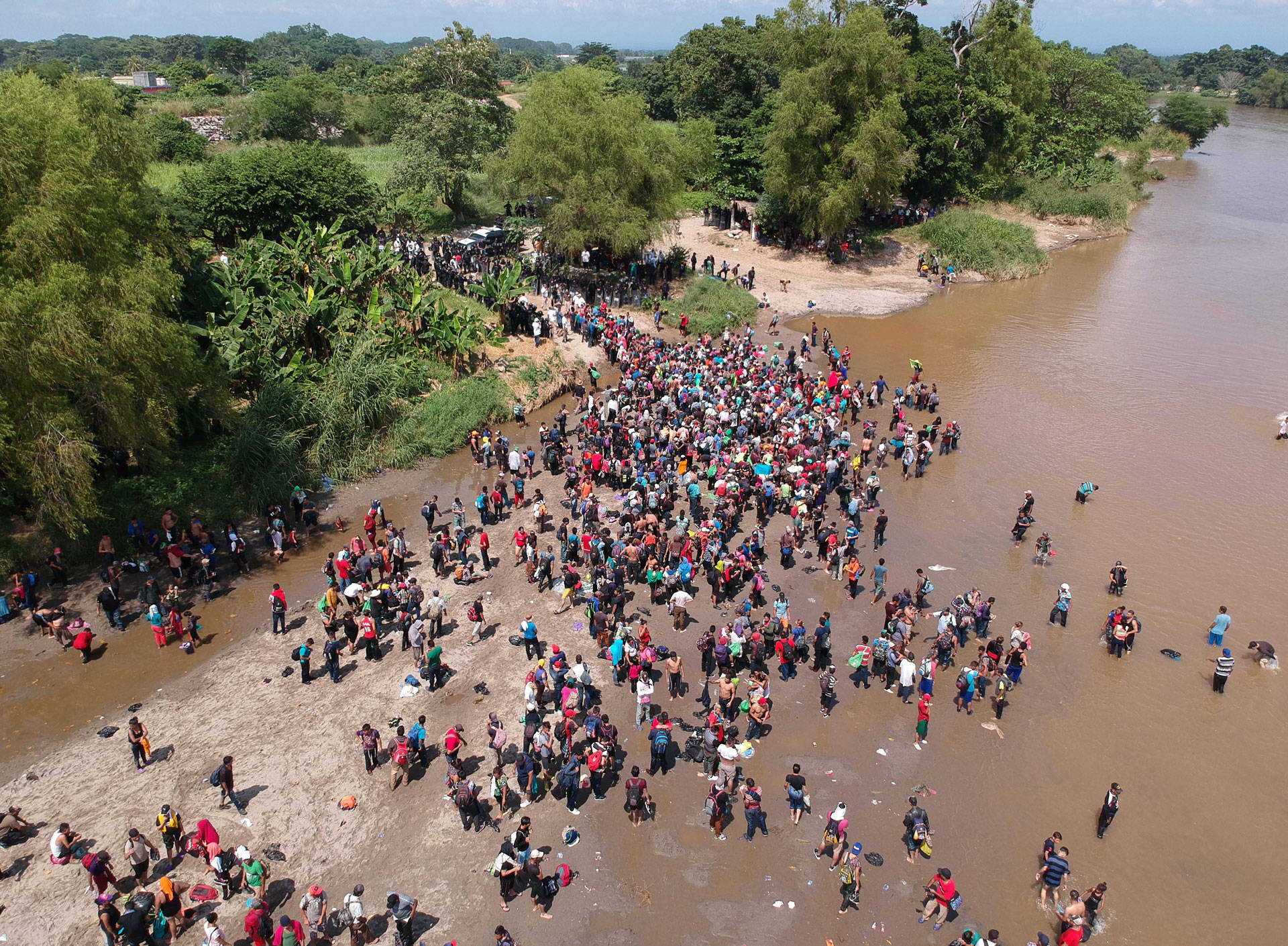 Migrants reach Mexico after crossing the Suchiate River from Tecun Uman in Guatemala to Ciudad Hidalgo in Mexico on Oct. 29, 2018, a day after a security fence on the international bridge was reinforced to prevent them from passing through. CARLOS ALONZO/AFP/Getty Images