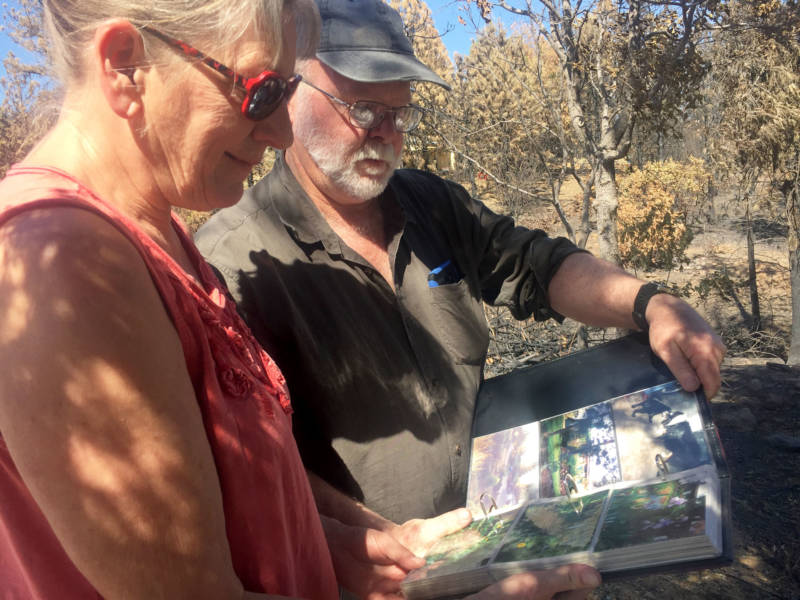Jim and Donna Dowling look at pictures of the lush gardens they maintained outside their home, before it was all destroyed in the Carr Fire.