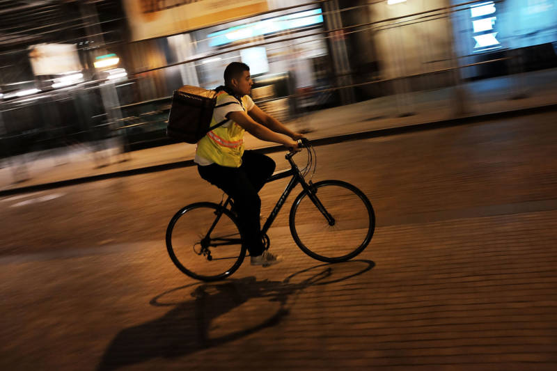 A third-party app food delivery worker transports food on his bicycle. Tacolicious co-owner Sara Deseran says third-party delivery apps have changed how she runs her restaurant.