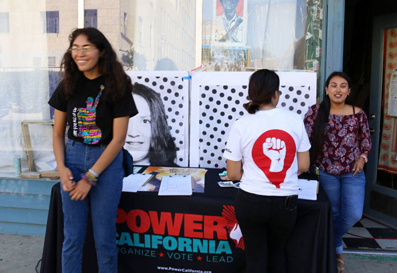 Valeria Mena (L) works the voter registration table at an art installation and Get Out the Vote event in downtown Fresno. Mena has been volunteering all summer to boost youth voter engagement in the Central Valley.