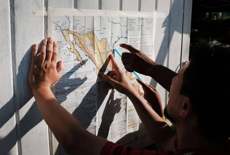 Some of the thousands of Central American migrants look at a map after arriving into the small town of Santiago Niltepec, Mexico on Oct. 29, 2018.