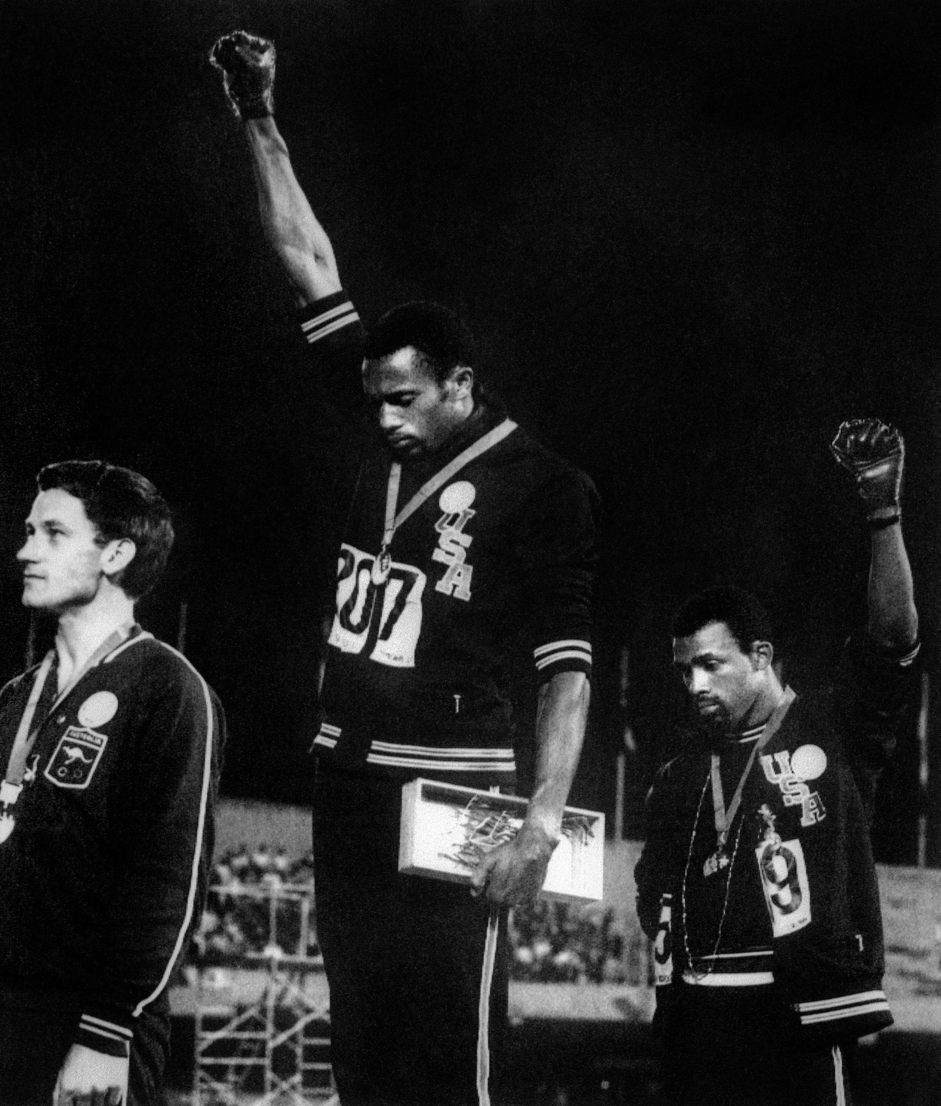 San Jose State University sprinter Tommie Smith, center, and John Carlos, right, raised their gloved fists on the awards podium at the 1968 Olympic Games in Mexico as a protest against racial oppression in America. Peter Norman of Australia, left, who took silver, wore an Olympic Project for Human Rights pin in solidarity.