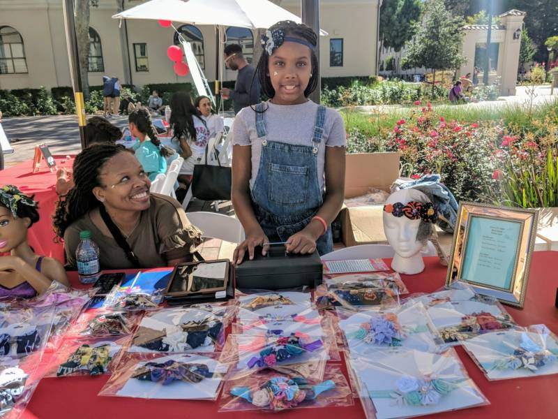 Jada Jackson from Oakland, 10, stands at her booth at the pop-up marketplace featuring young girl entrepreneurs. She was selling her handmade headbands and hairbows.