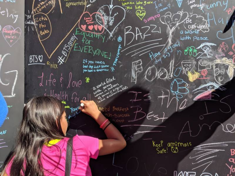 A young girl writes on a response board at the Girls' Festival. 'We call it a day of power and possibility. As women and girls we need to know there are so many opportunities for us to shine, and expand, and become leaders,' said Maureen Broderick, founder and CEO of WorldWideWomen, which organized the event.