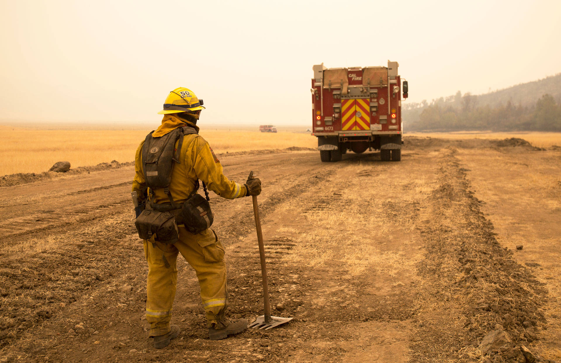 A Cal Fire firefighter watches for spot fires from a controlled burn at the edge of the Ranch Fire in 2018. Anne Wernikoff/KQED