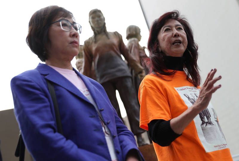 Retired judges Julie Tang (L) and Lillian Sing (R), co-charis of the Comfort Women Justice Coalition, speak during a news conference next to the 'Column of Strength' statue on Oct. 3, 2018.