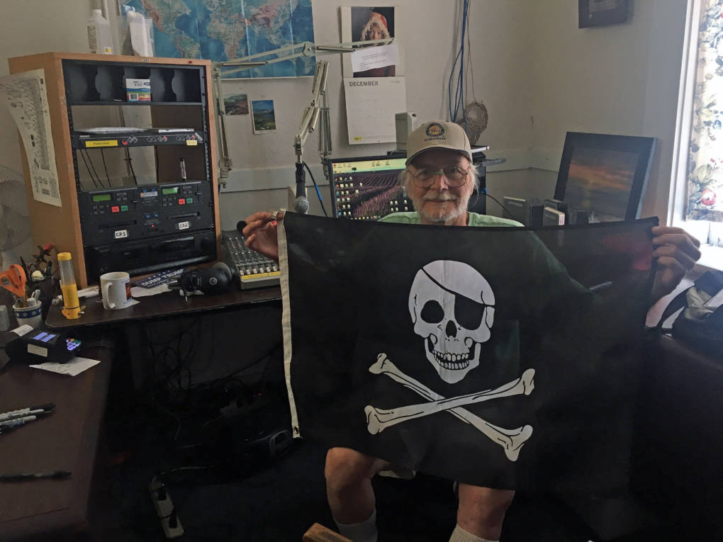 KPFZ station manager Andy Weiss holds up a pirate flag.