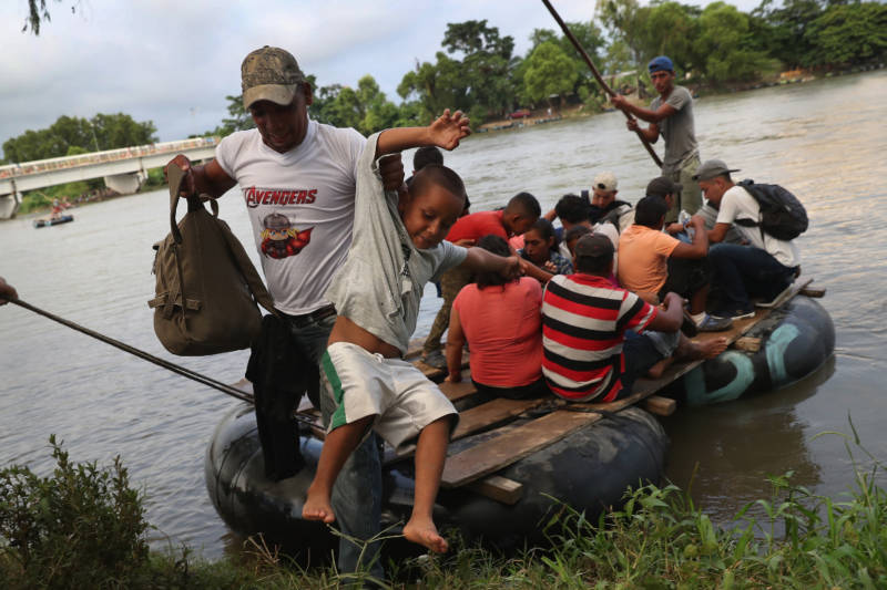 Migrant families cross into Mexico using a raft to avoid the Mexican officials perched on the bridge above the Suchiate River.