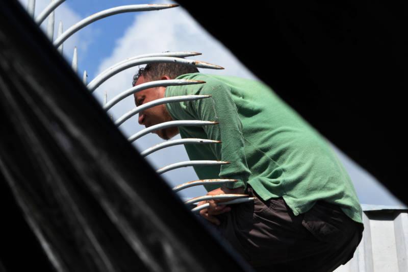 A Honduran migrant attempts to cross the border fence from Ciudad Tecun Uman, Guatemala, to Ciudad Hidalgo, Mexico, on Sunday.