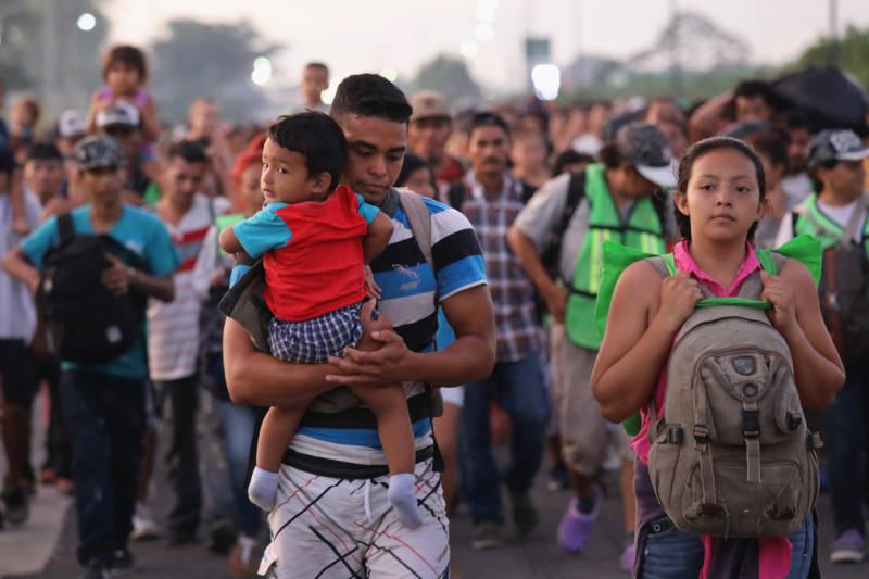 Members of a migrant caravan carry their children on the walk deeper into Mexico after crossing the Guatemalan border Sunday.