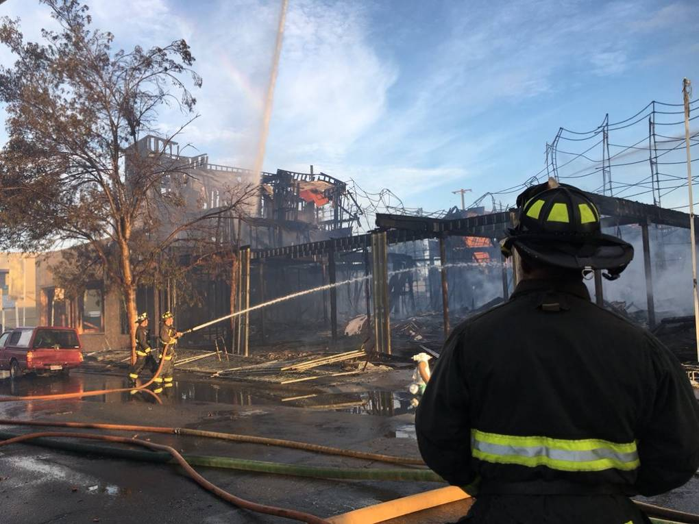 """Oakland firefighters on scene at Tuesday morning's blaze at an under-construction town home development at West Grand Avenue and Myrtle Street. <a href=""""https://twitter.com/oaklandpoliceca"""" target=""""_blank"""">Oakland Police Department</a> via Twitter"""