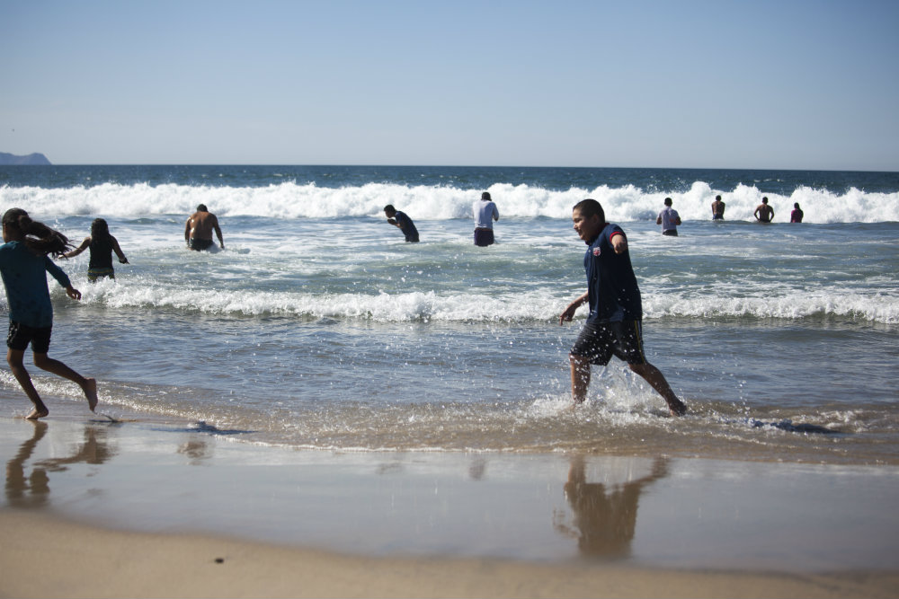 Migrant adults and children whooped and splashed around at Playas De Tijuana, located right next to the border fence on Wednesday, November 14, 2018. Erin Siegal McIntyre/KQED
