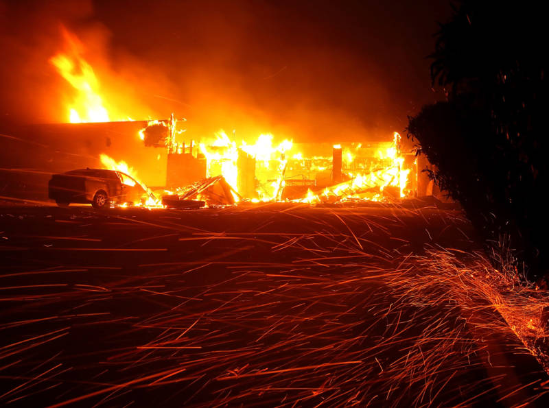 Embers blow in the wind as the Camp Fire burns a restaurant on Nov. 8, 2018 in Paradise.