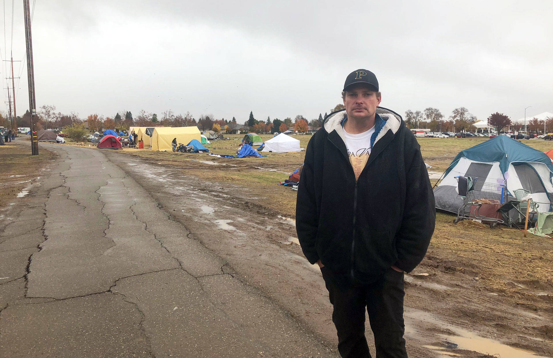 Ulis Gordon stands by several dozen tents outside a Chico Walmart where some Camp Fire survivors are staying. Sonja Hutson/KQED