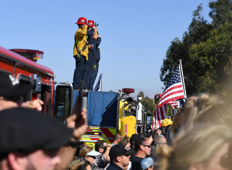 Firefighters salute as they watch a motorcade procession transporting the body of Sheriff's Sergeant Ron Helus on Nov. 8, 2018.