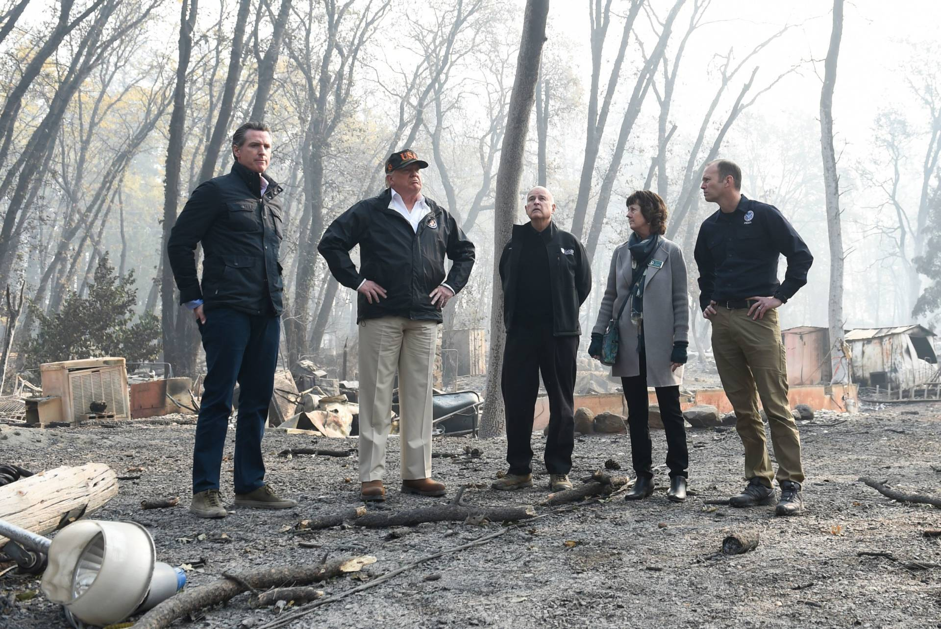 US President Donald Trump (2L) looks on with Paradise Mayor Jody Jones (2R), Governor of California Jerry Brown (C), Administrator of the Federal Emergency Management Agency, Brock Long (R), and Lieutenant Governor of California, Gavin Newson, as they view damage from wildfires in Paradise, California on November 17, 2018. - President Donald Trump arrived in California to meet with officials, victims and the 'unbelievably brave' firefighters there, as more than 1,000 people remain listed as missing in the worst-ever wildfire to hit the US state. SAUL LOEB/AFP/Getty Images