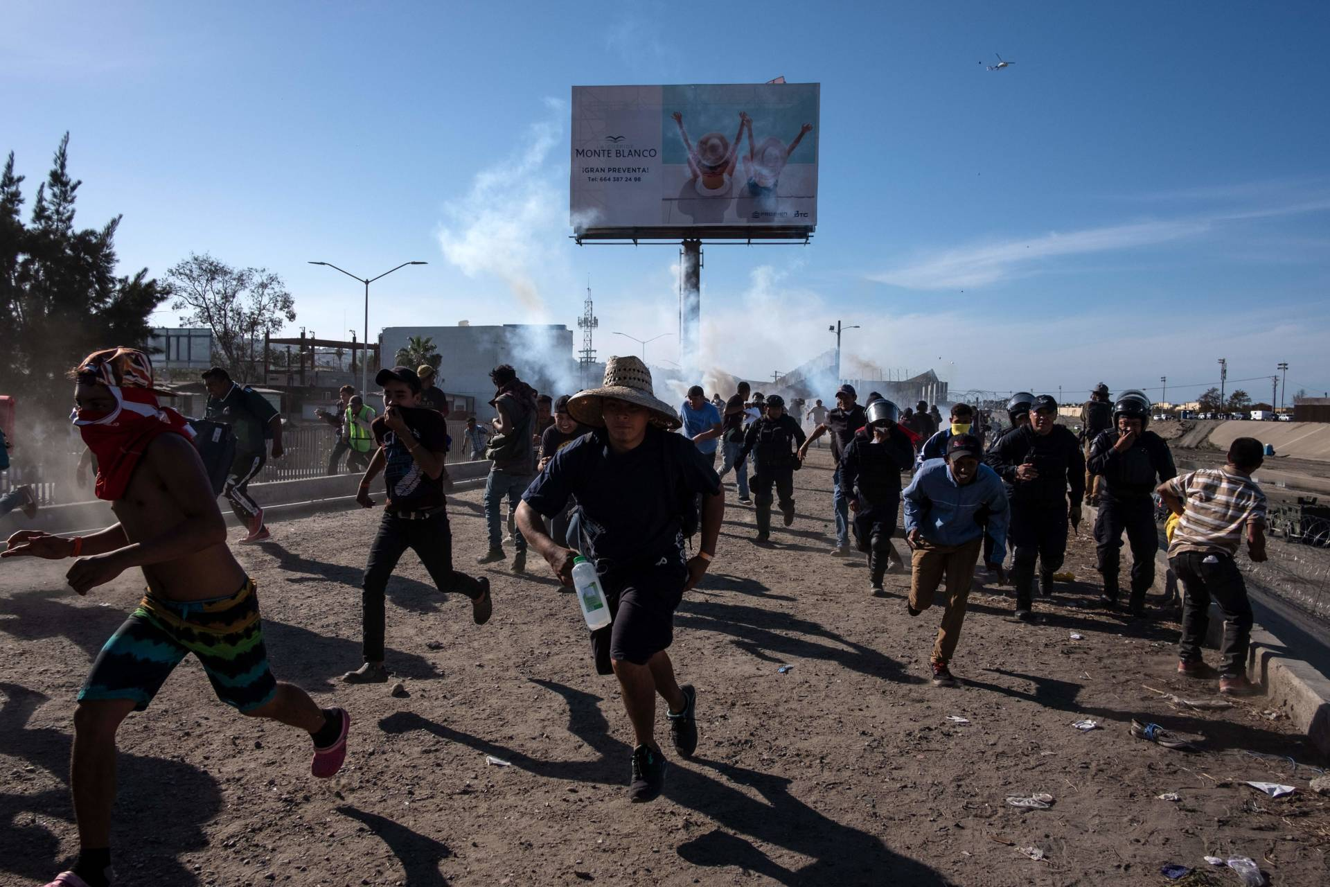 Central American migrants, mostly Hondurans, run along the Tijuana River near the El Chaparral border crossing after U.S. border agents threw tear gas from a distance to disperse them after an alleged verbal dispute on Nov. 25, 2018. Guillermo Arias/AFP/Getty Images
