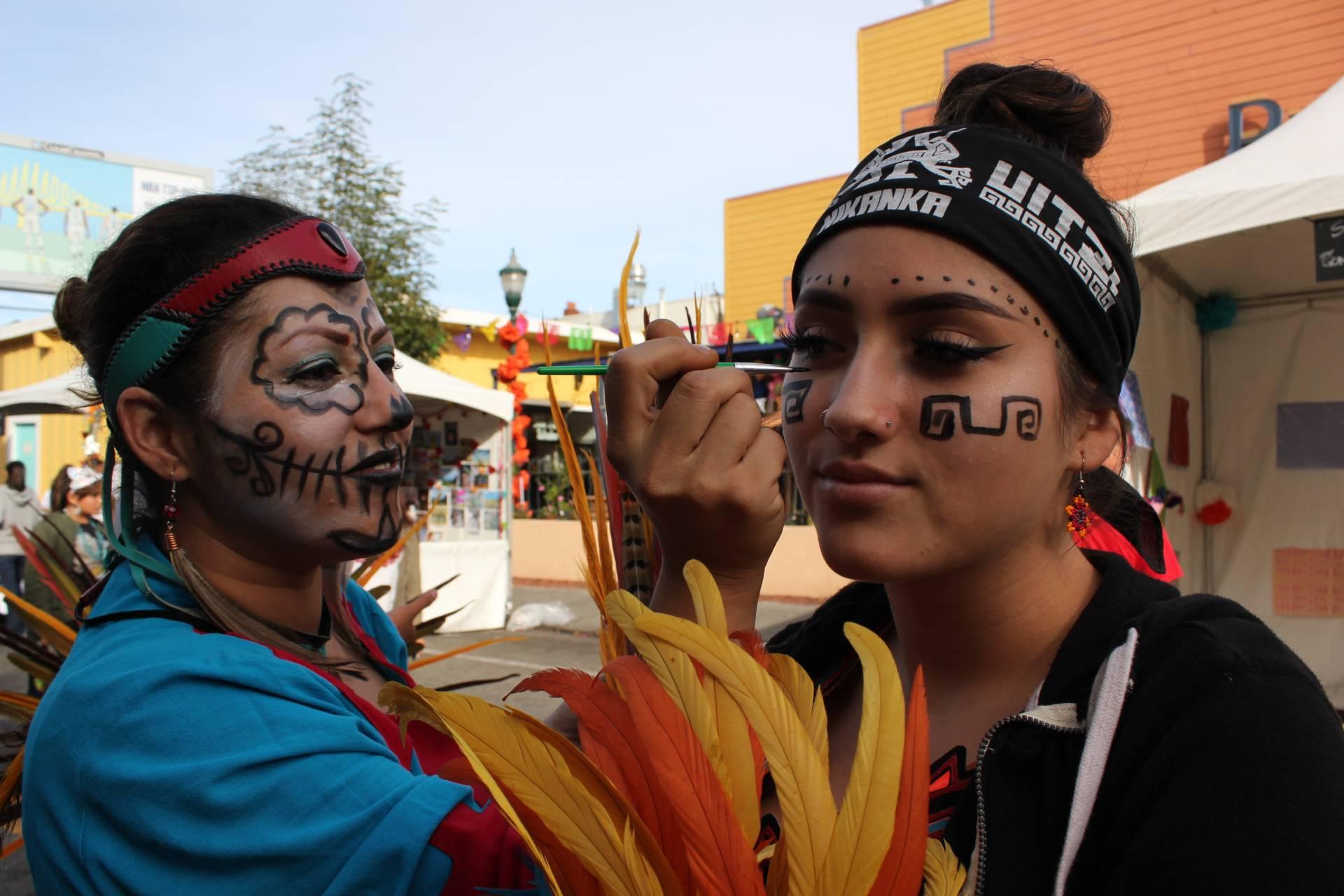 Maricela Sandoval of San Jose paints the face of fellow dancer, Estrella Zamudio, also of San Jose. Sara Hossaini/KQED
