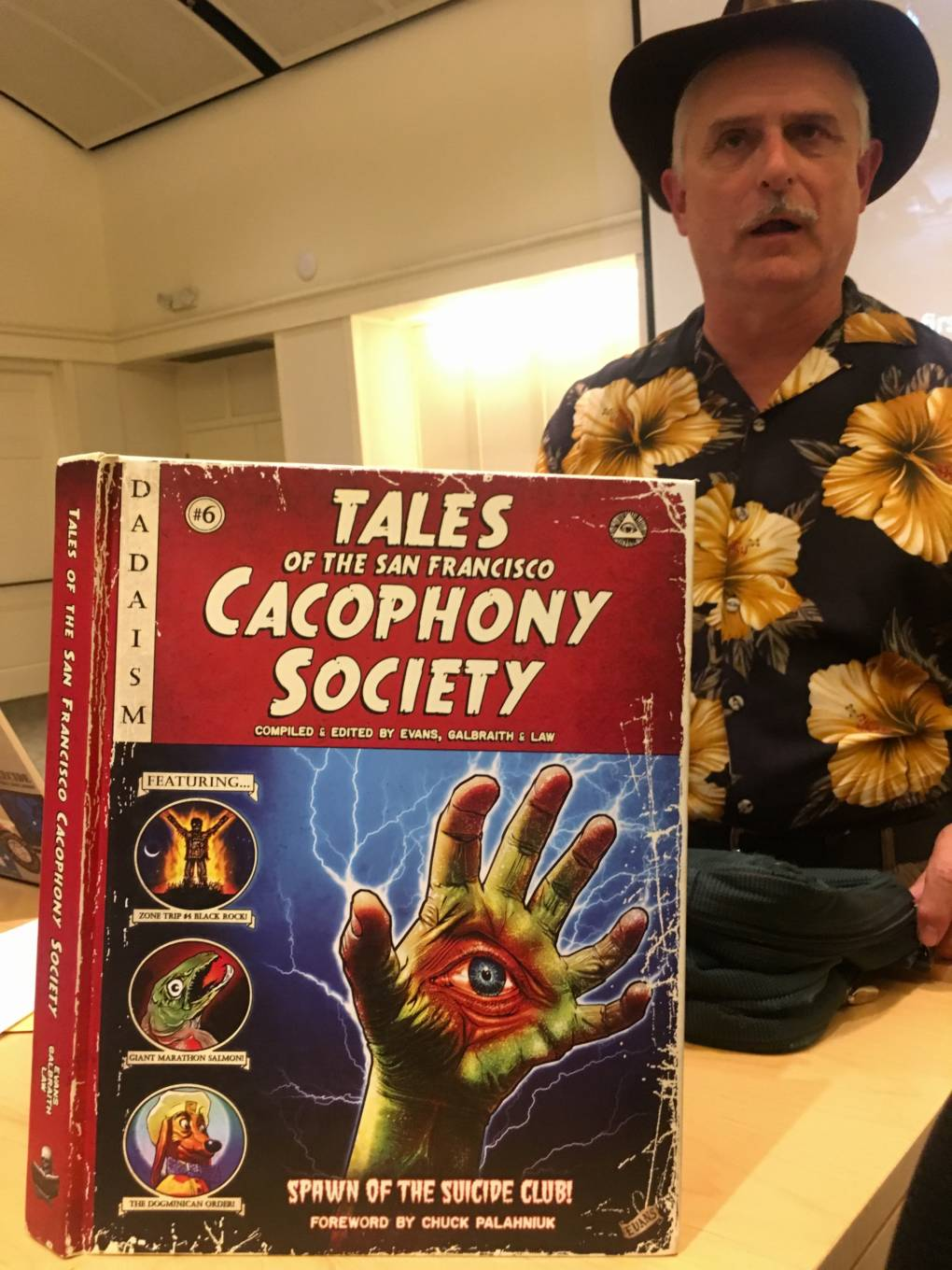 John Law stands behind a book about the Cacophony Society.
