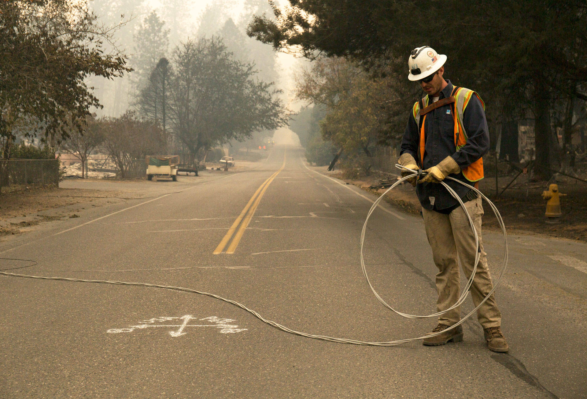 A PG&E worker clears fallen power cables from a road in the Butte County town of Paradise after the Camp Fire swept through the community in November 2018.  Anne Wernikoff/KQED