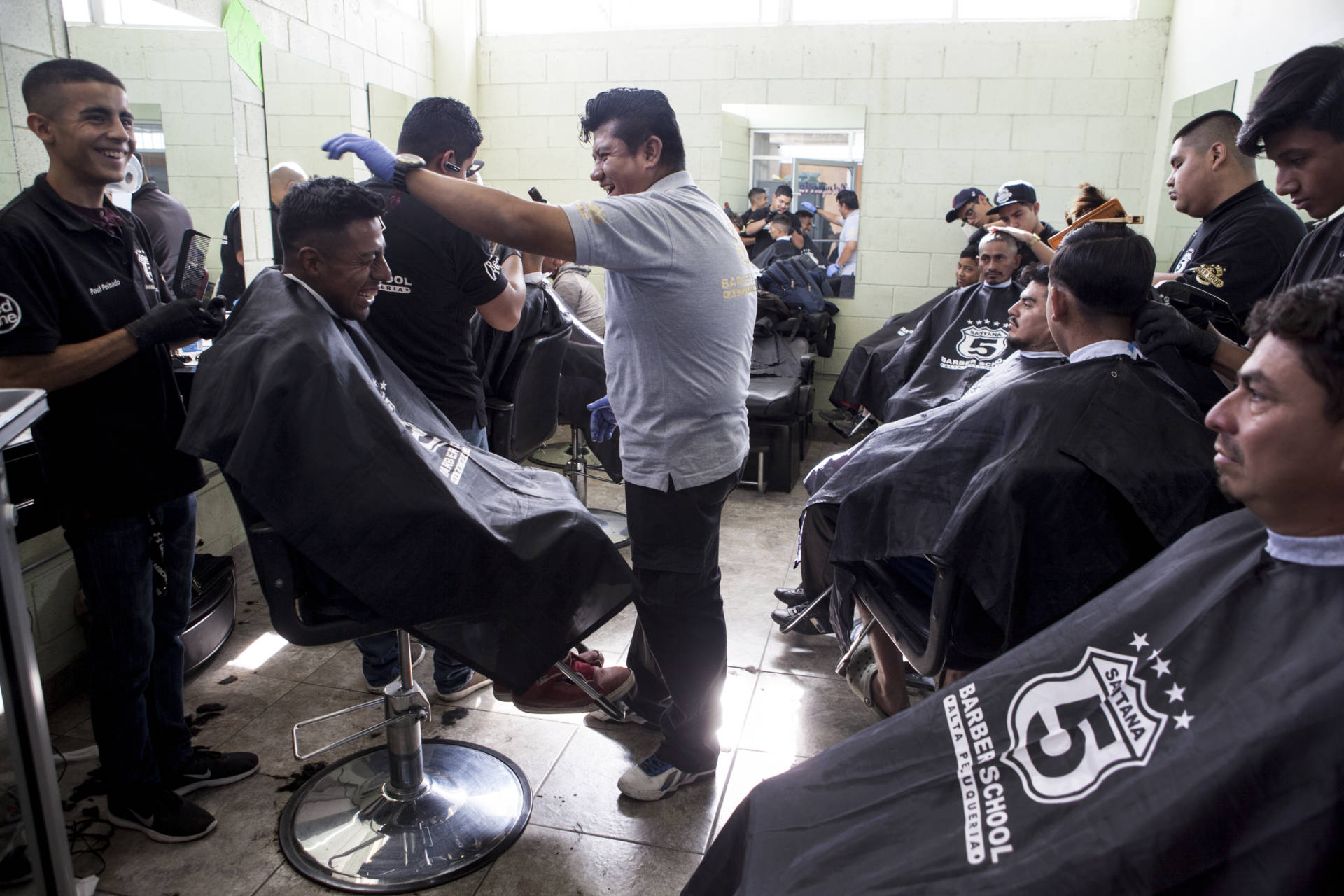Thousands of Central American migrants traveling together through Mexico to reach the U.S. border arrived in Tijuana Thursday, Nov. 15, 2018. At a Catholic center called Padre Chava, migrants received breakfast and free haircuts from students of Santana 5 Barber School. The school has provided free haircuts at the shelter for years.   Erin Siegal McIntyre/KQED