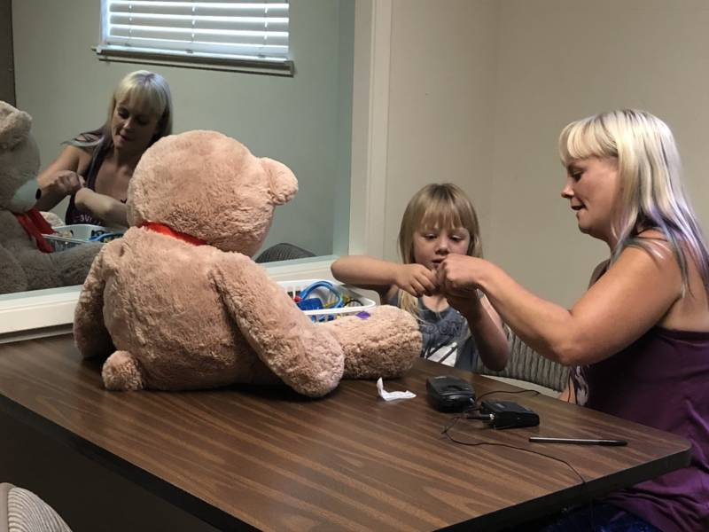 Sabrina Hanes and daughter Aroara during a Parent-Child Interaction Therapy session. Mother and daughter sit on one side of a two-way mirror. A therapist, sitting on the other side of the mirror, coaches Hanes through an earbud she wears.