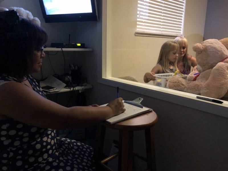 Therapist Laurie Taylor observes mother and daughter from behind the two-way mirror.