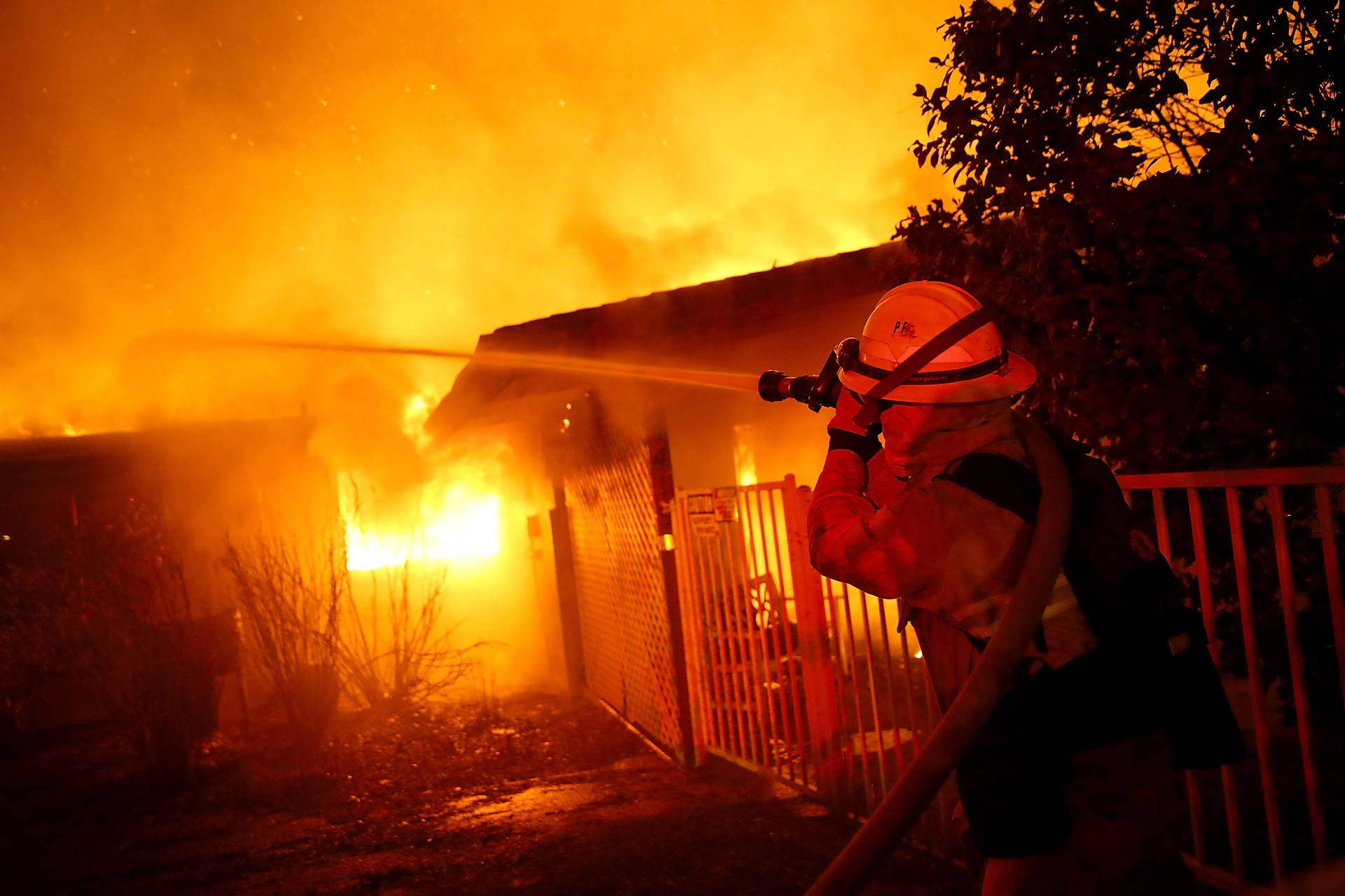 Firefighters try to contain a fire so it doesn't spread to a neighboring building as the Camp Fire burned in the community of Paradise on Nov. 8, 2018.  Justin Sullivan/Getty Images