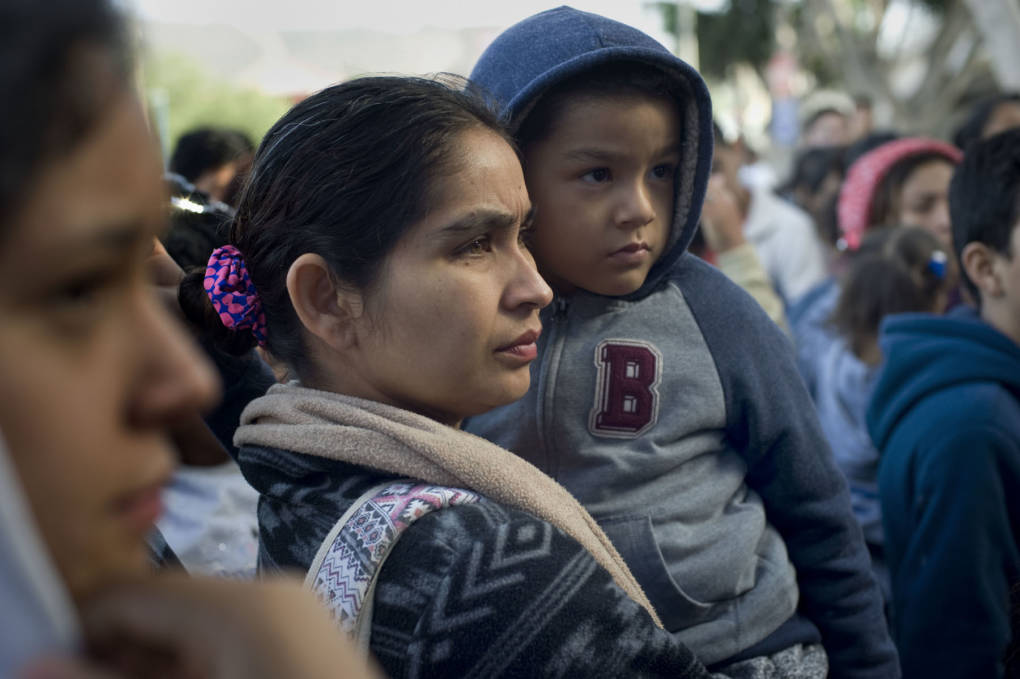 A woman and child in Tijuana, Mexico, wait to hear their position on a list of people hoping to seek asylum in the U.S. on Nov. 21, 2018 David Maung/KQED