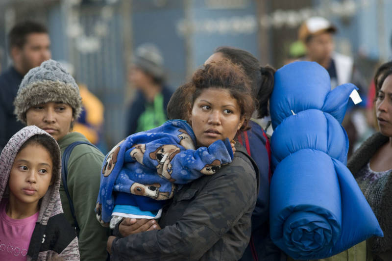 Migrant families who arrived in Tijuana with the caravan wait in line to enter a city sports complex converted into a shelter, on Nov. 20, 2018.