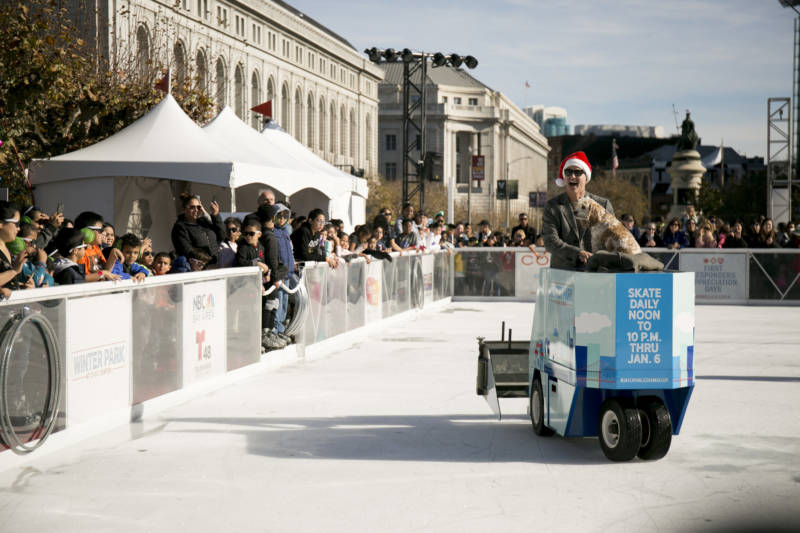 Figure skater and Olympic gold medalist Brian Boitano rides around the rink on a Zamboni with his dog Hunter before charging through the ribbon to officially open the rink.