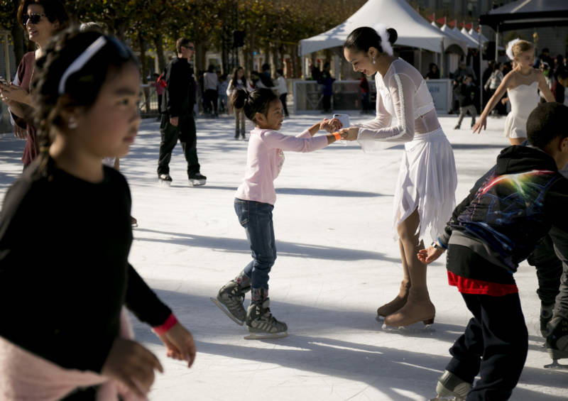 A performer from San Francisco Ice Theatre helps a young girl balance on her skates as other children skate around the rink.