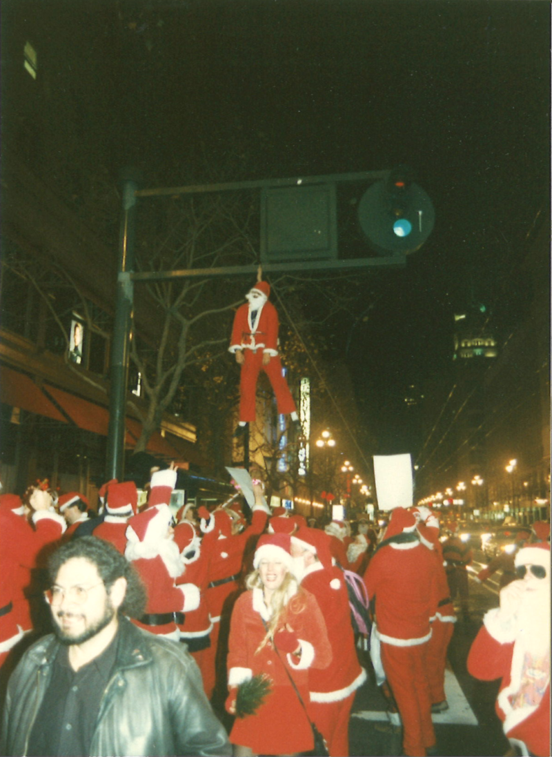 John Law hangs from a light wearing a harness underneath his suit.