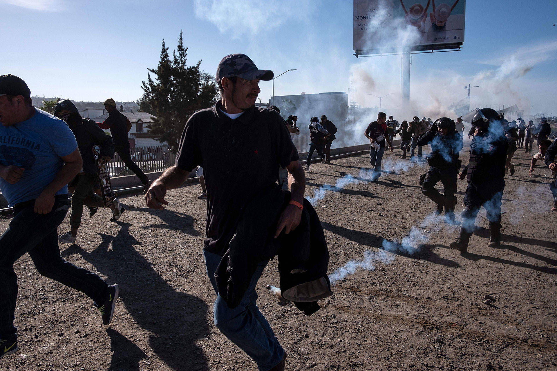 Central American migrants run along the Tijuana River near the El Chaparral border crossing in Tijuana, Mexico, after U.S. border agents launched tear gas to disperse them on Nov. 25, 2018. GUILLERMO ARIAS/AFP/Getty Images