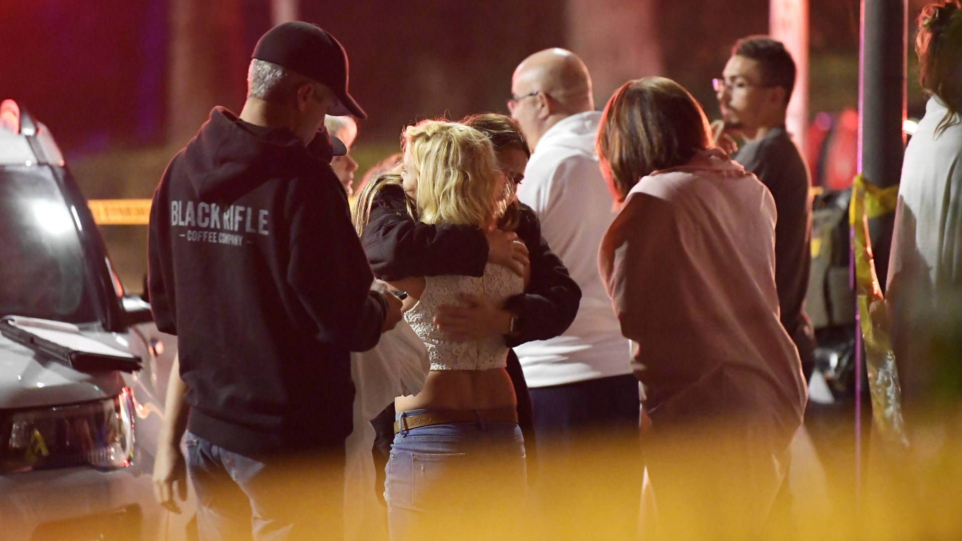 People comfort each other outside a bar in Thousand Oaks, where a gunman opened fire and killed 12. Mark J. Terrill/AP