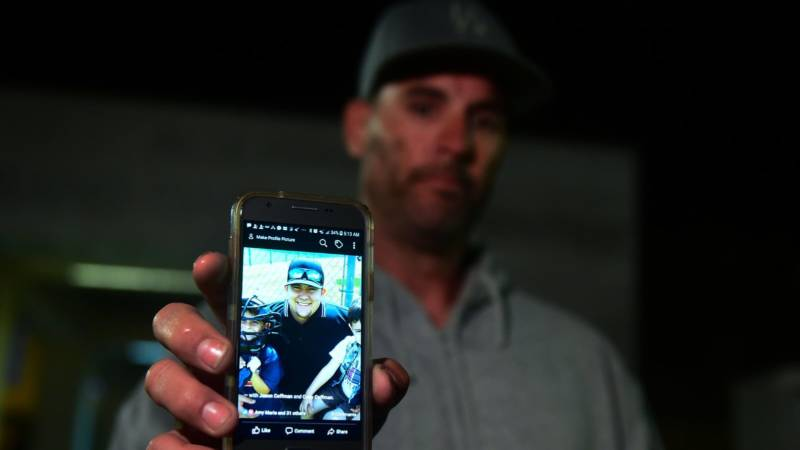 Jason Coffman displays a photo outside the Thousands Oaks Teen Center as he tried to locate his son Cody, who was at the Borderline Bar and Grill in Thousand Oaks, Calif.