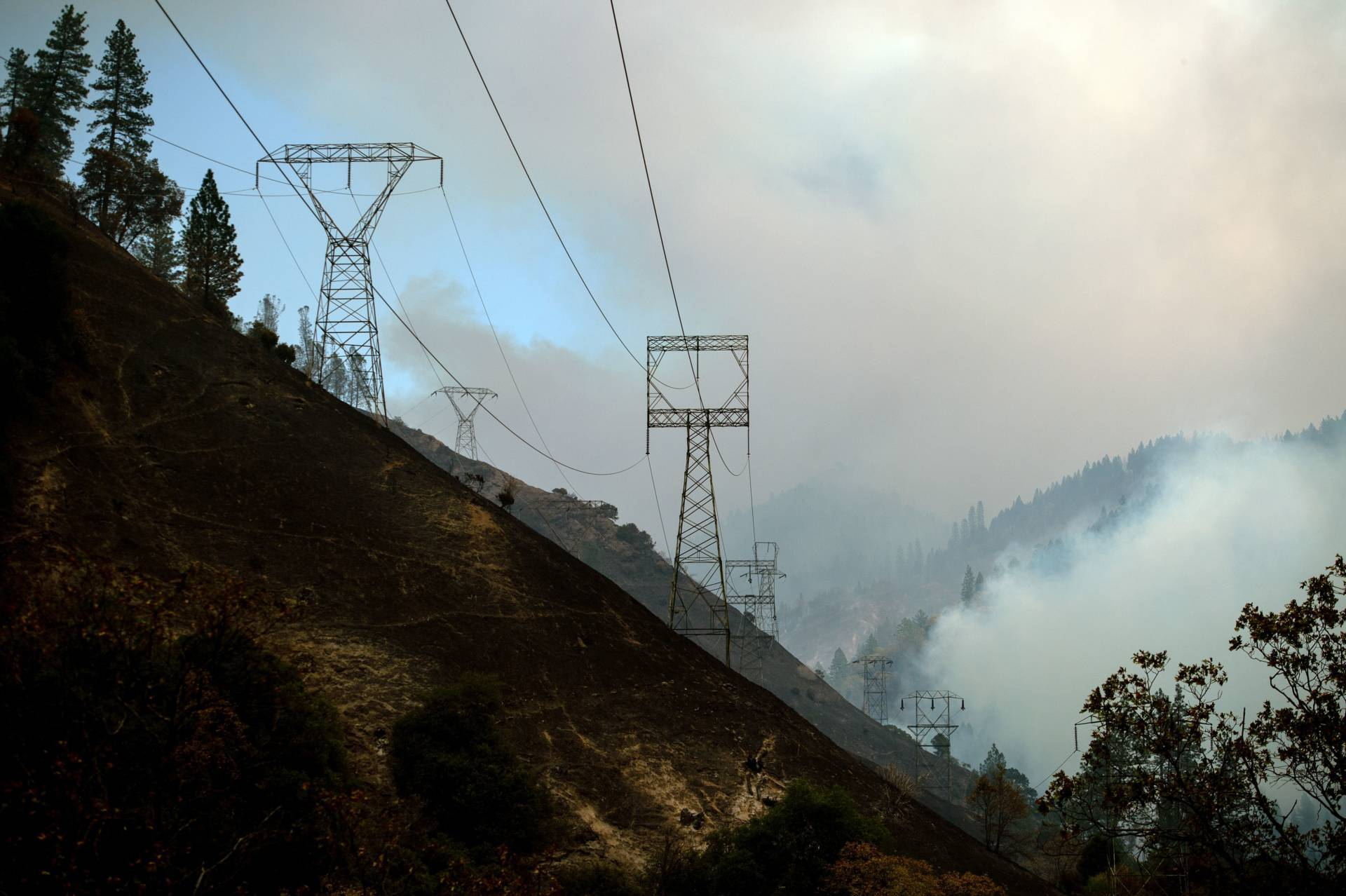 PG&E transmission  towers on the Caribou-Palermo line are seen against a smoky landscape adjacent to the Feather River in Butte County last November. The towers are close to the spot where officials say the Camp Fire began. Josh Edelson/AFP-Getty Images