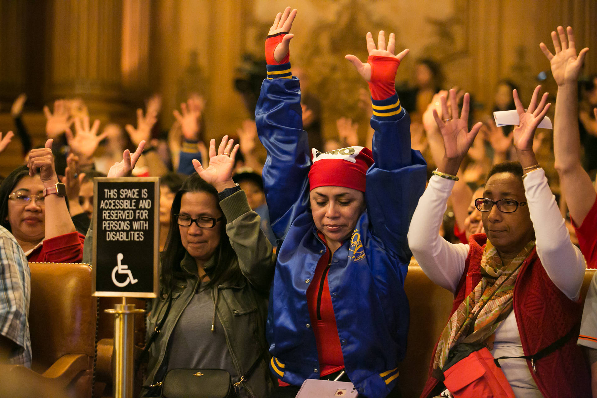 Camucha King (middle right) and Nicole Drysdale (right) gesture in affirmation to a speaker during the public comment section of the San Francisco Board of Supervisors meeting on Nov. 2, 2018. King and Drysdale work at the St. Regis hotel in the food and beverage department. J.P. Dobrin/KQED