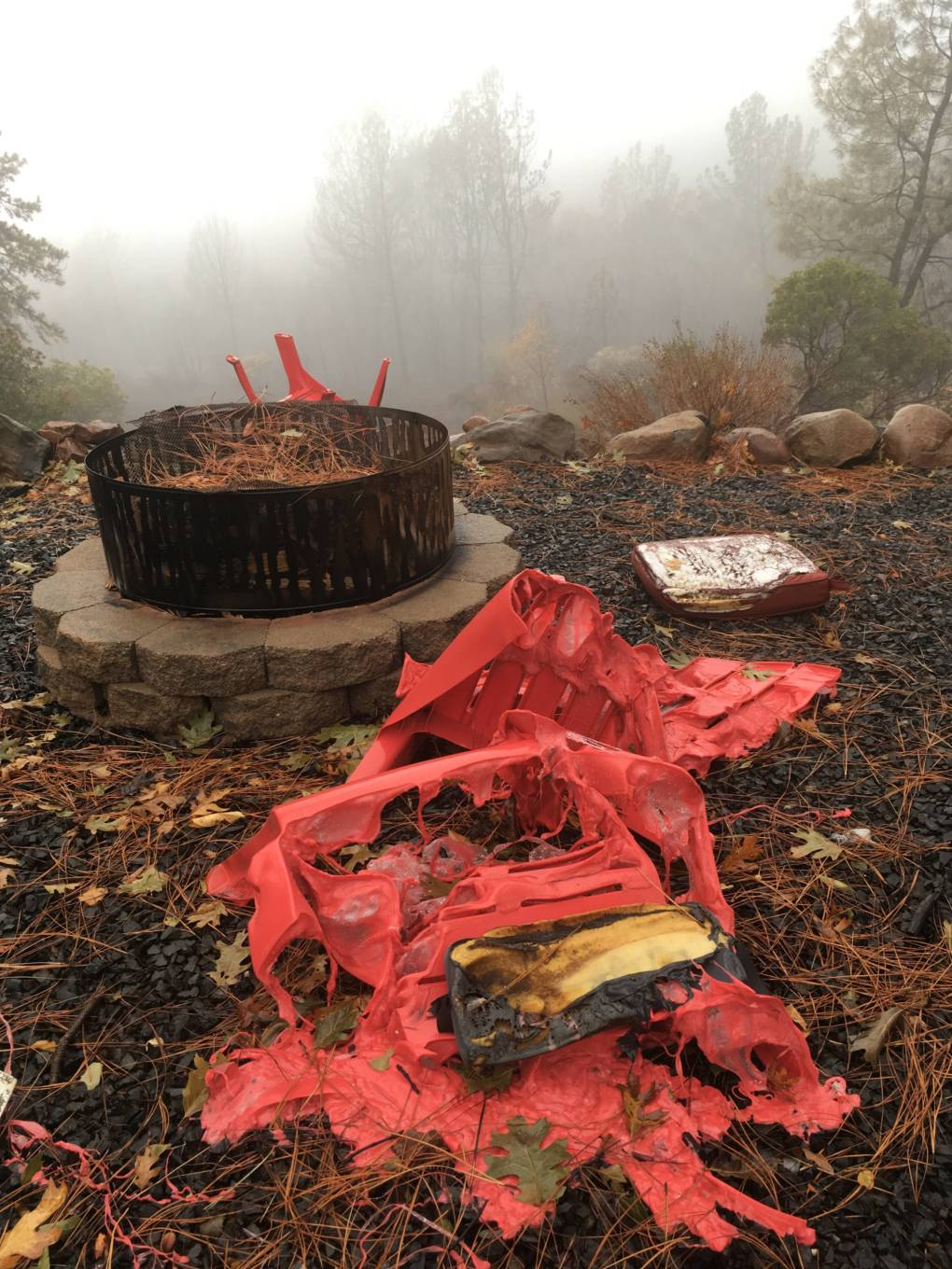 A melted lawn chair sits by the fire pit. (KQED/Myrow)