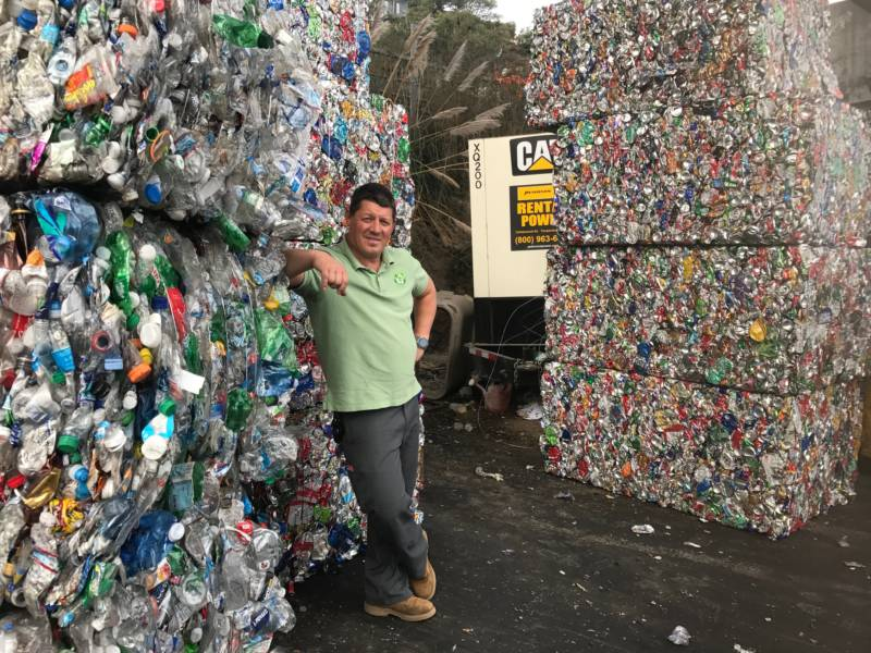Ors Csaszar, owner of Our Planet Recycling SF, stands besides bales of cans and bottles.