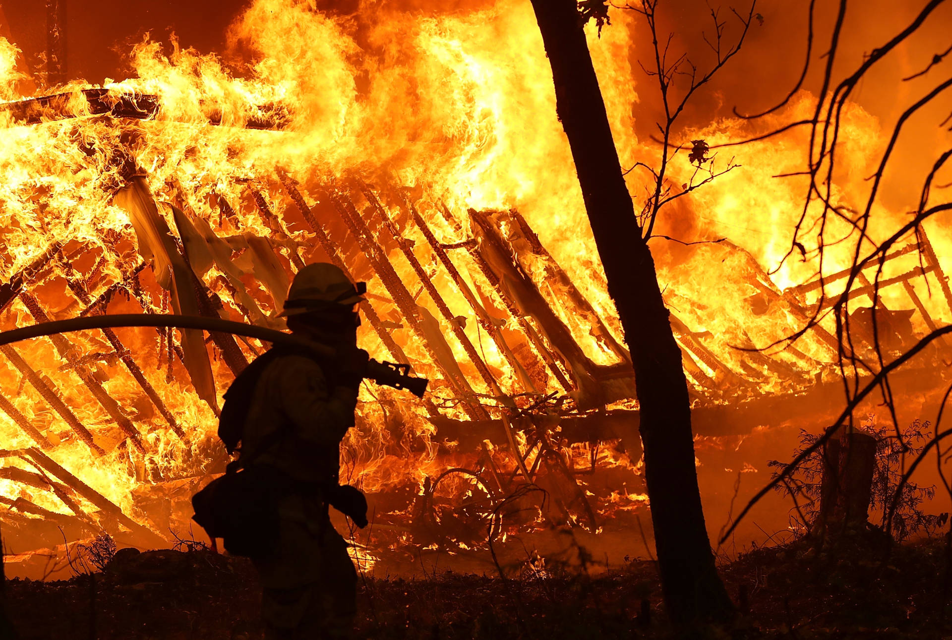 A Cal Fire firefighter monitored a burning home as the Camp Fire moved through Magalia on Nov. 9.  Justin Sullivan/Getty Images