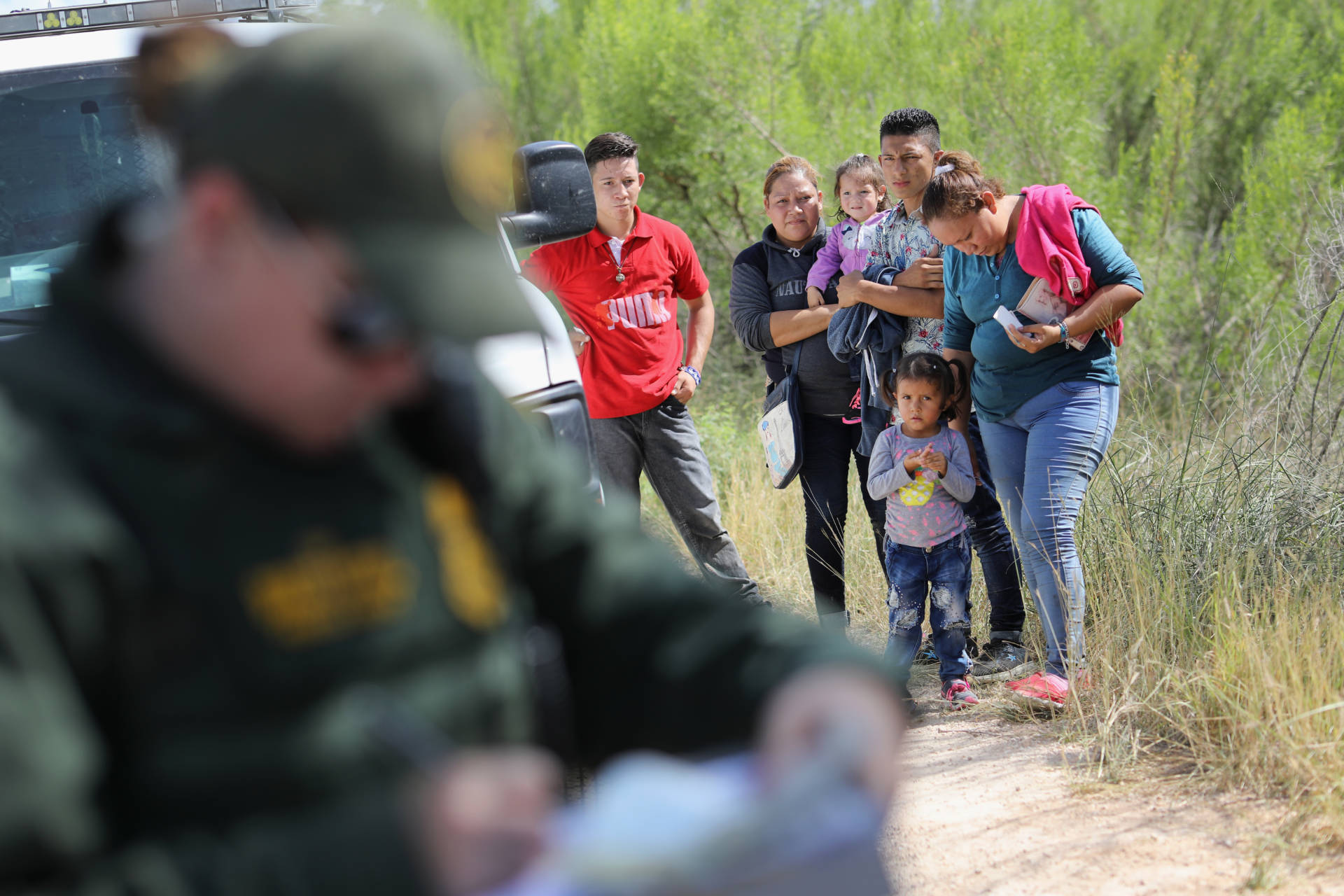 Central American asylum-seekers wait as U.S. Border Patrol agents take groups of them into custody on June 12, 2018, near McAllen, Texas. The families were then sent to a U.S. Customs and Border Protection processing center for possible separation.  John Moore/Getty Images