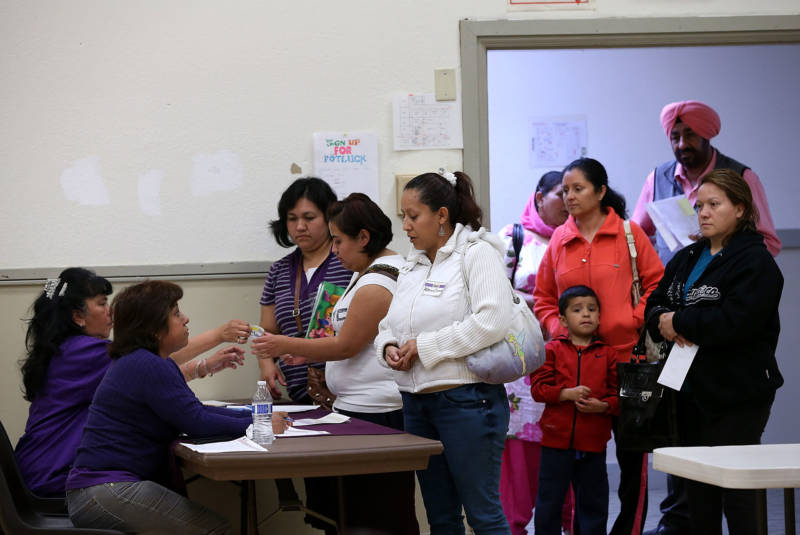 People wait to register for helath care insurance during an enrollment fair on March 28, 2014 in Bay Point.
