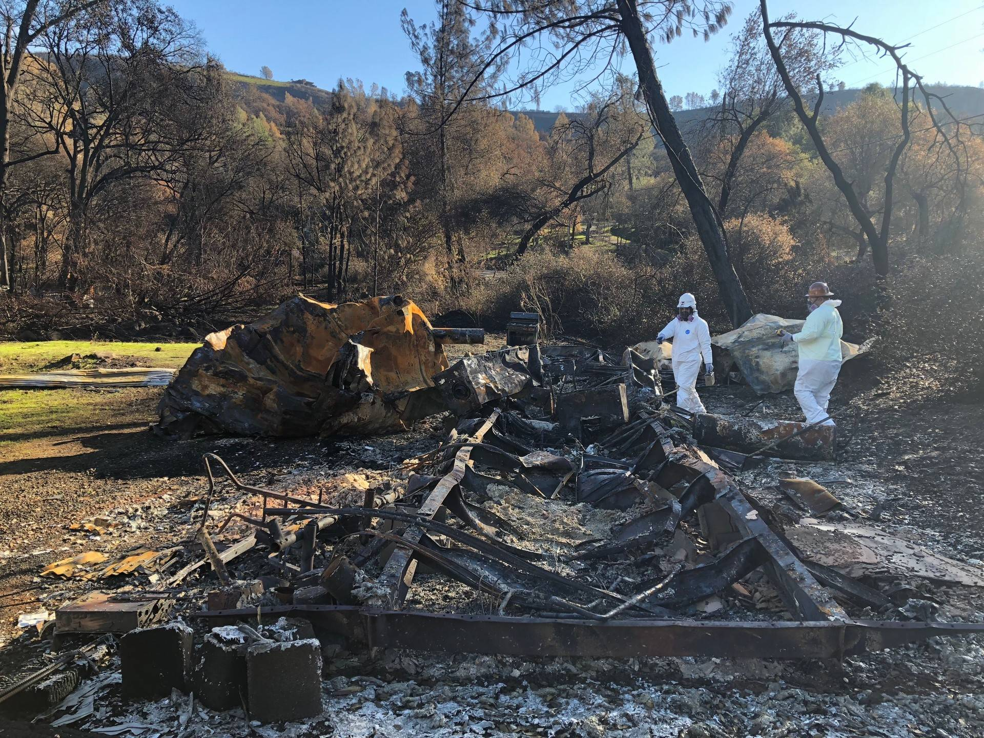 EPA workers use a radiation detector and multi-gas meter to search for hazardous waste in a mobile home destroyed by the Camp Fire. Sonja Hutson/KQED