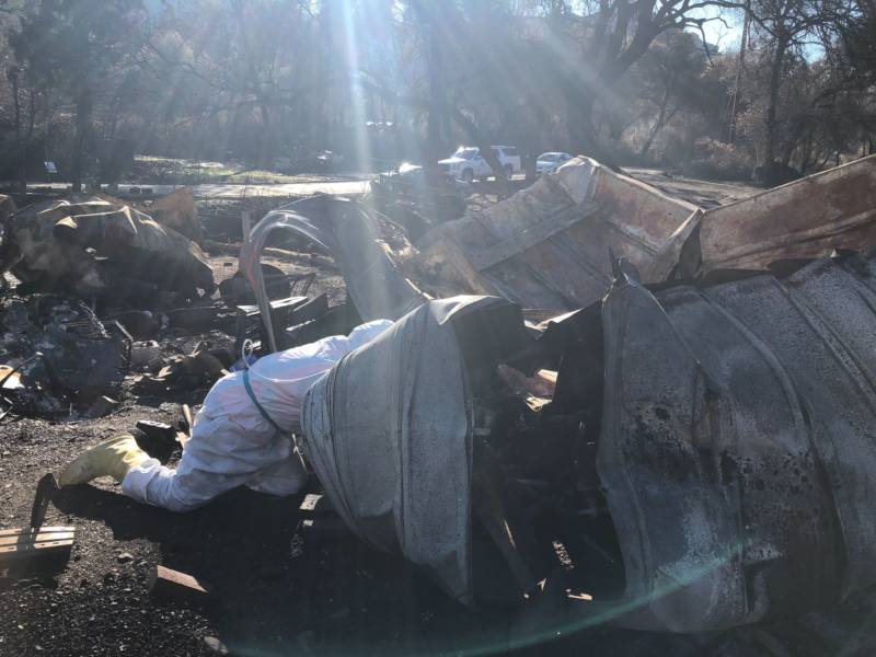 An EPA worker crawls into the remnants of a mobile home burned by the Camp Fire to look for hazardous material to remove.