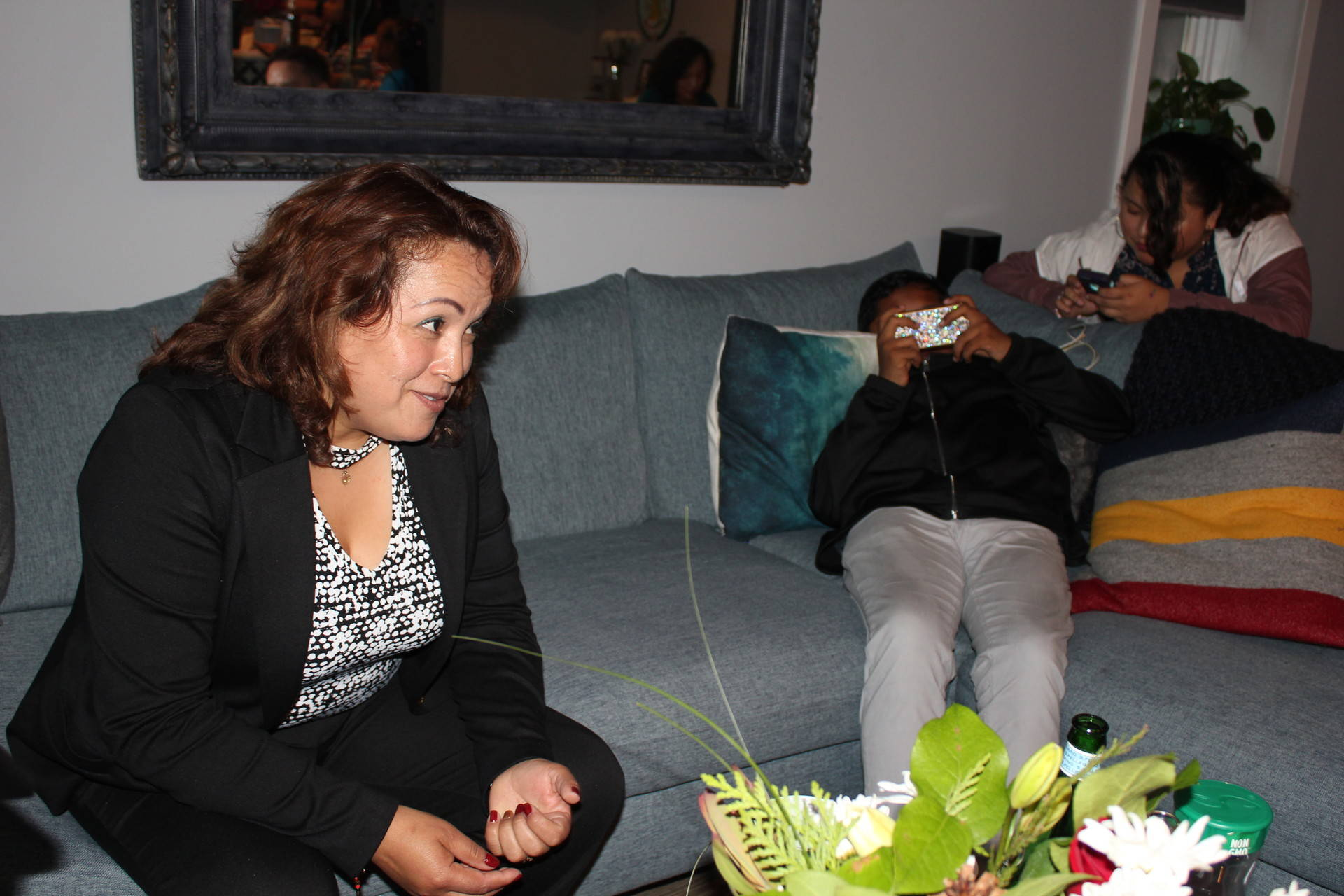 Maria Mendoza-Sanchez (L) sits on a couch in her attorney's home with two of her four children after returning to the United States from Mexico following a 16-month deportation. Sara Hossaini/KQED