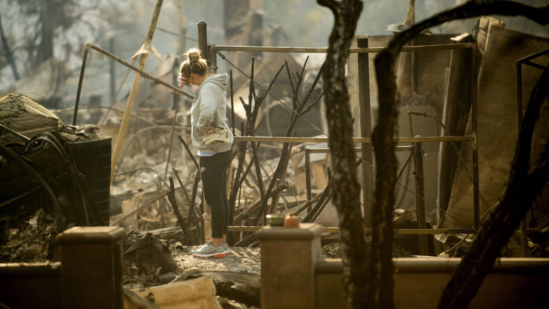 Bree Laubacher pauses while sifting through rubble at her Ventura, Calif., home following the Thomas Fire in December 2017.