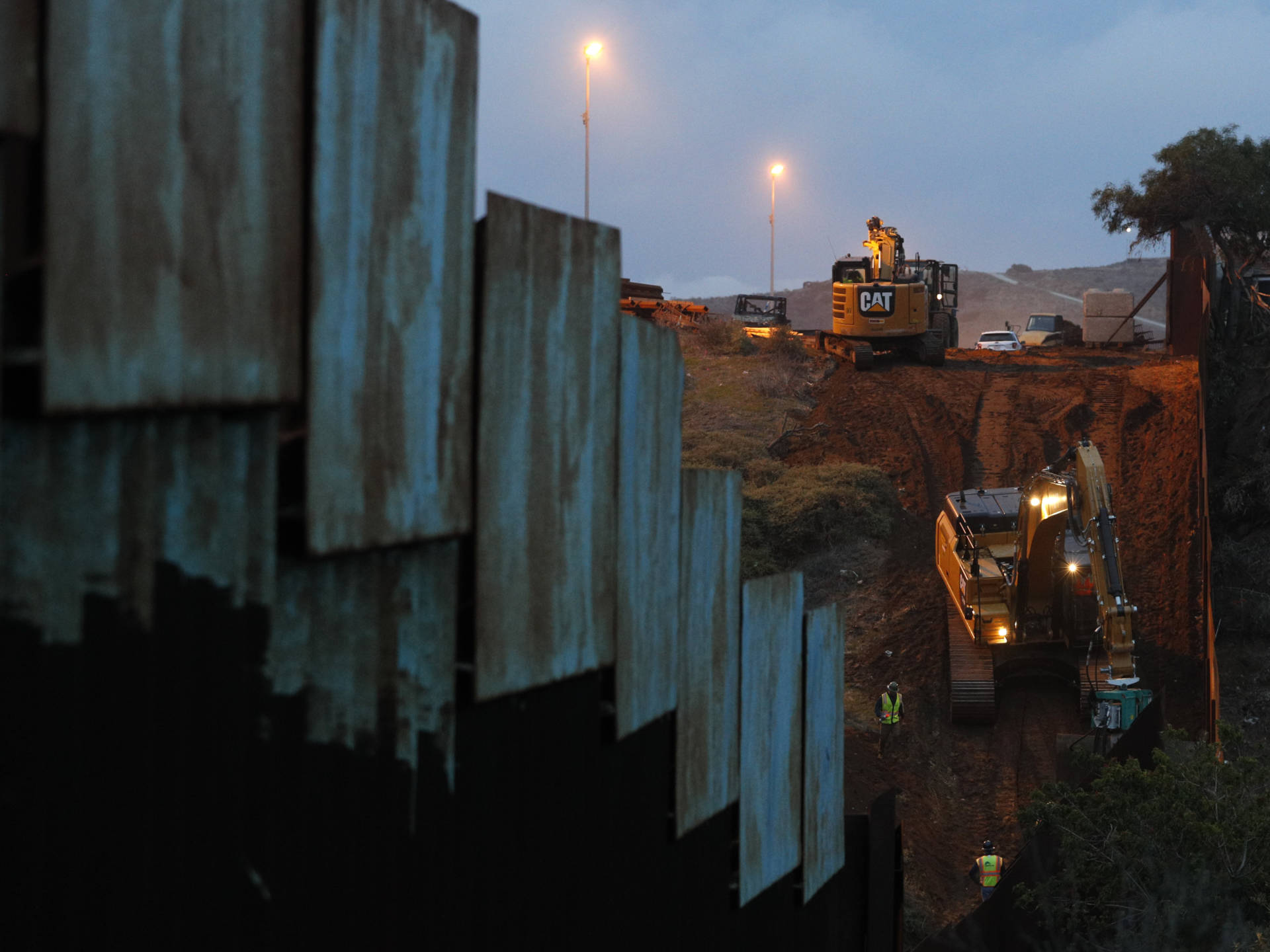 Contractors work to reinforce a section of the U.S. border wall in San Diego where scores of Central American migrants have crossed illegally in recent weeks, photographed through the fence from Tijuana, Mexico. Rebecca Blackwell/AP