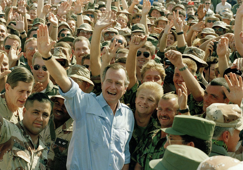 President Bush poses with soldiers during a stop at an air base in Dhahran, Saudi Arabia, on Nov. 22, 1990.